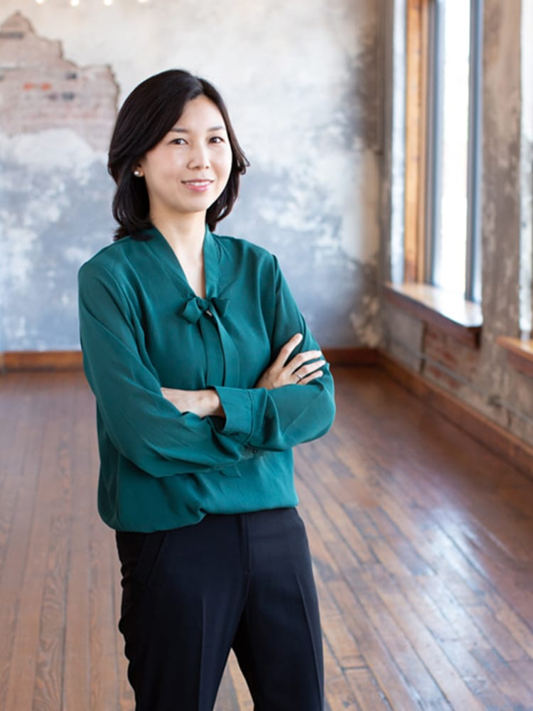 Photo of Buhyun Kim wearing a green blouse and black pants.