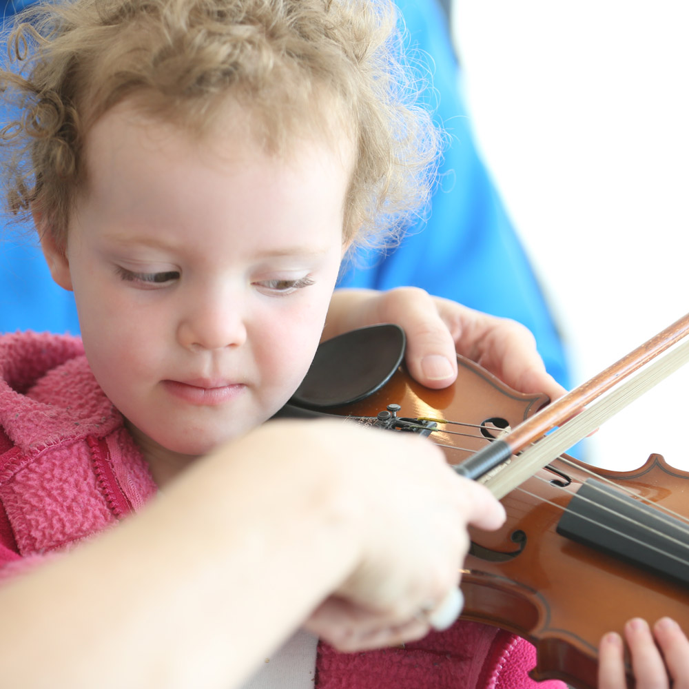 child learning to play violin