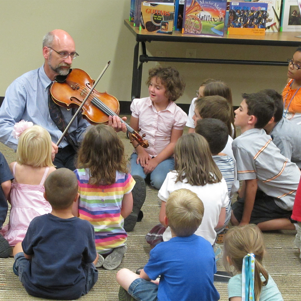 man playing violin with children