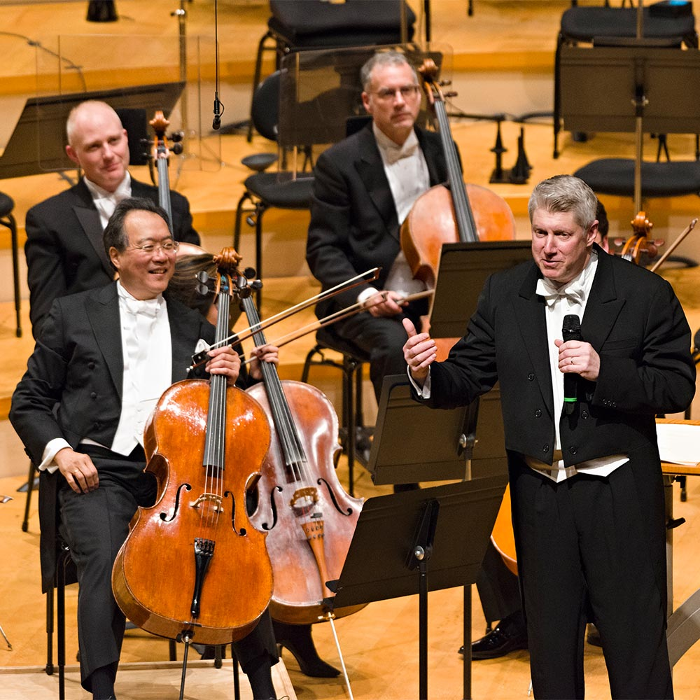 Michael Stern addresses a Kansas City Symphony audience on stage in Helzberg hall with yo yo ma at his side.