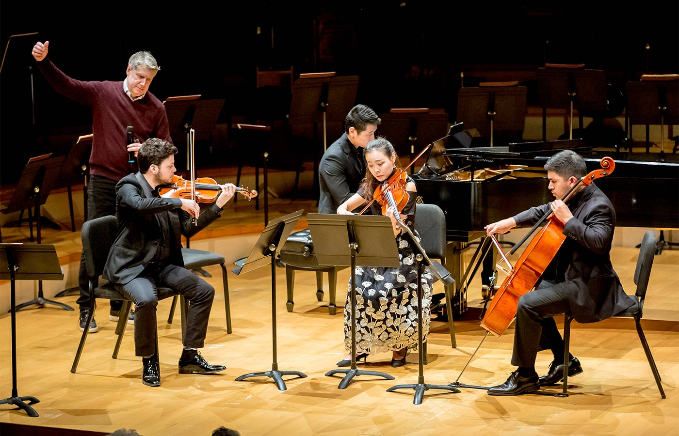 Photo of Michael Stern with a student chamber music group on stage in Helzberg Hall