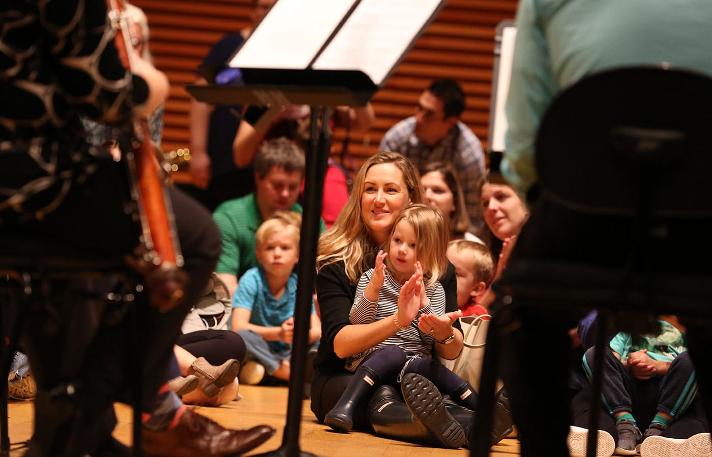 Mother and child sitting on stage in Helzberg Hall listening to Kansas City Symphony musicians perform at a Petite Performance