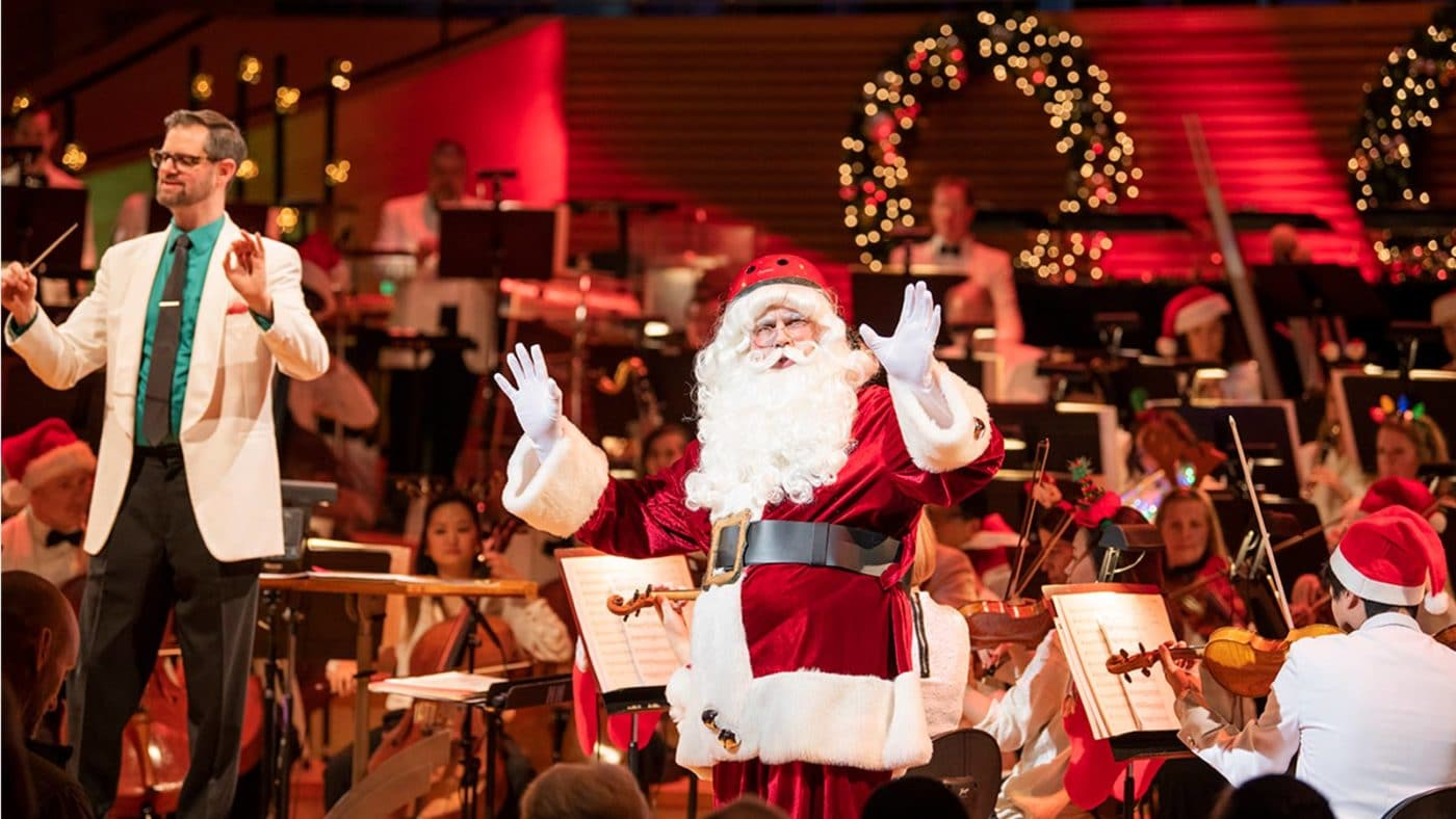 Photo of Jason Seber, Santa Claus and the Kansas CIty Symphony on stage in Helzberg Hall at Christmas Festival