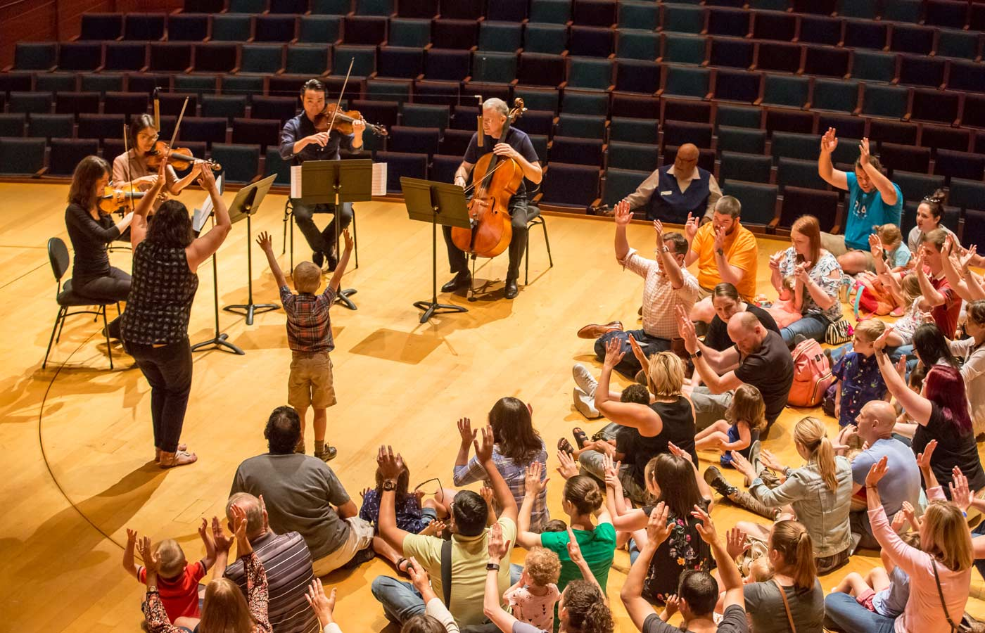 Photo of Kansas City Symphony musicians and audience on stage in Helzberg Hall at a Petite Performance