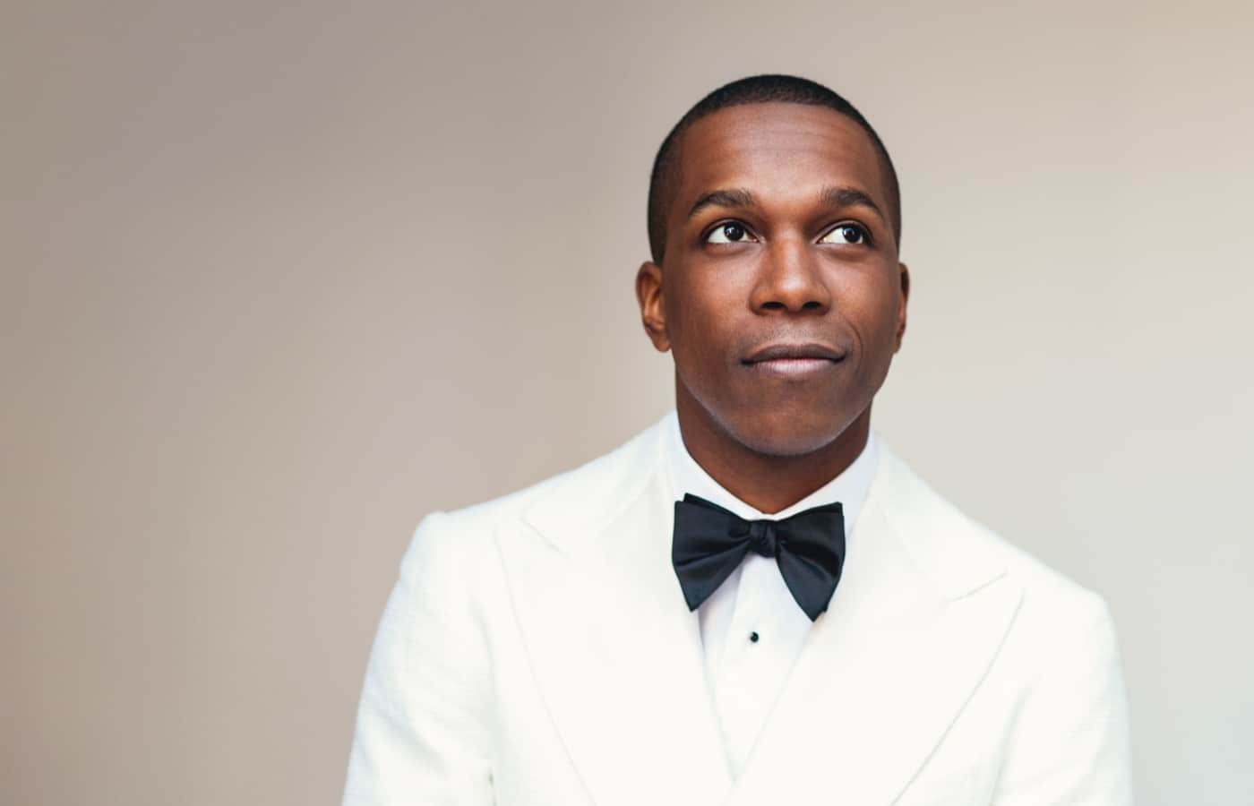 Photo of vocalist Leslie Odom, Jr. in a white tuxedo