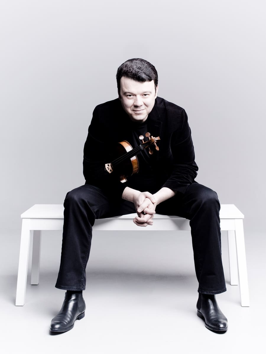 Photo of violinist Vadim Gluzman sitting on a white bench in a white room holding his violin under his right arm.