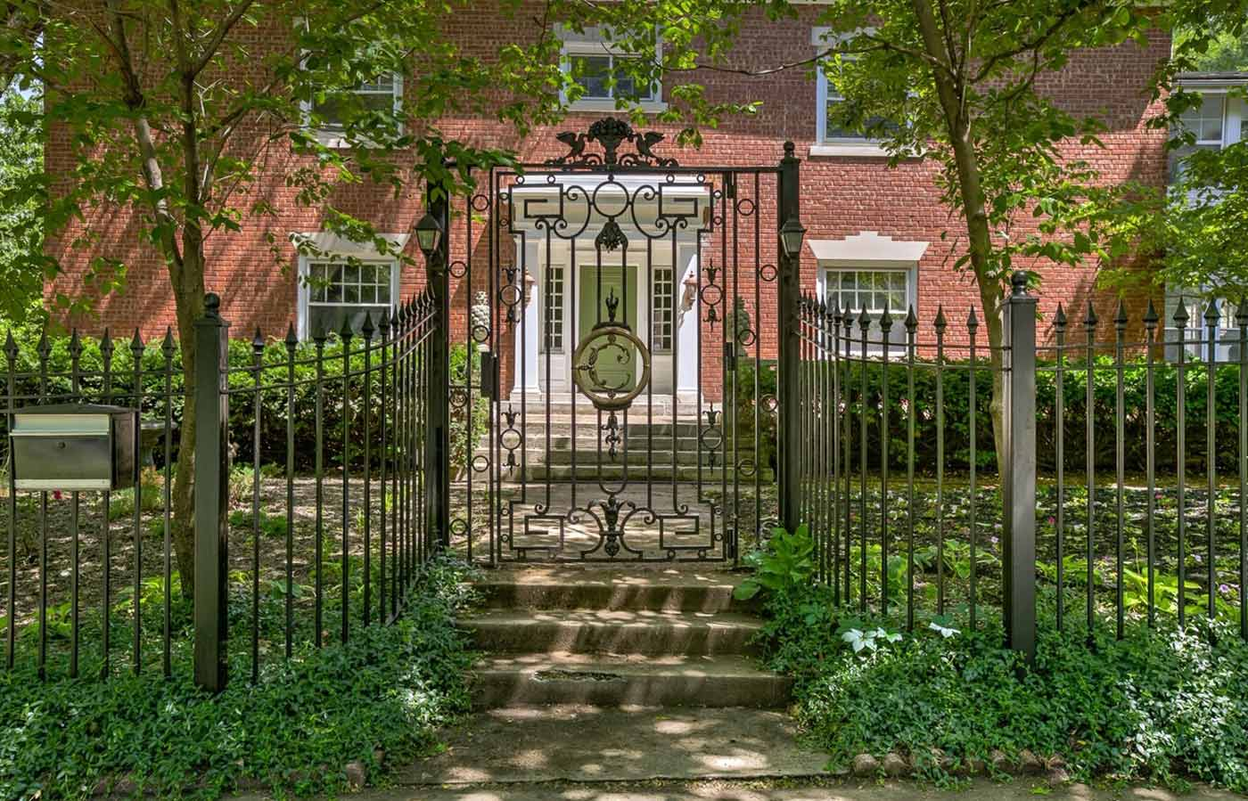 Photo of the 2019/20 Symphony Designers' Showhouse in Kansas City. A brick home with wrought iron fence