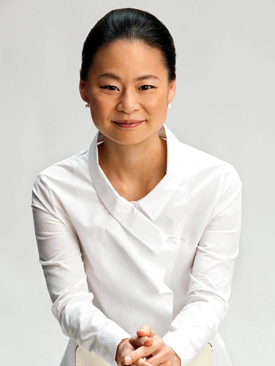 Photo of Violinist Midori wearing a white ensemble with a white background