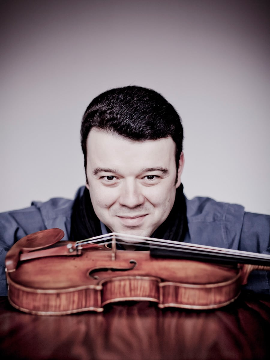 Photo of violinist Vadim Gluzman staring over his violin which is sitting on the table in front of him