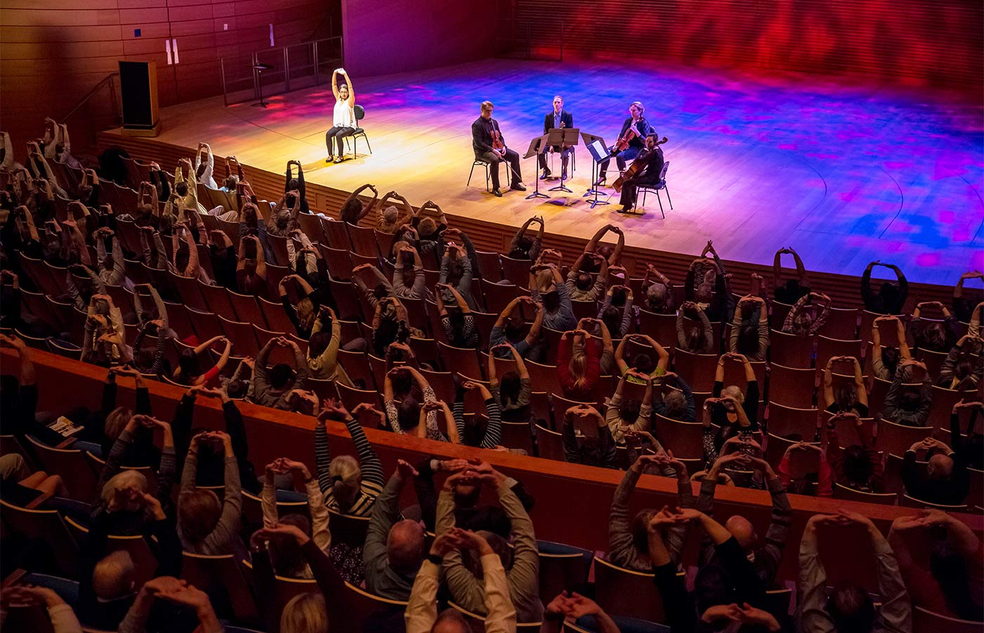 Photo of people participating in a guided meditation event with a string quartet. In Helzberg Hall at Kauffman Center for the Performing Arts