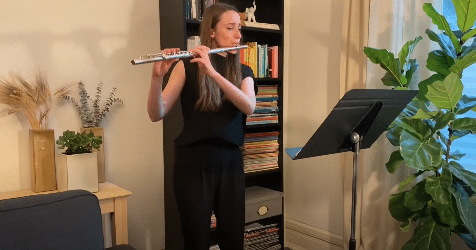 Kayla playing flute in living room